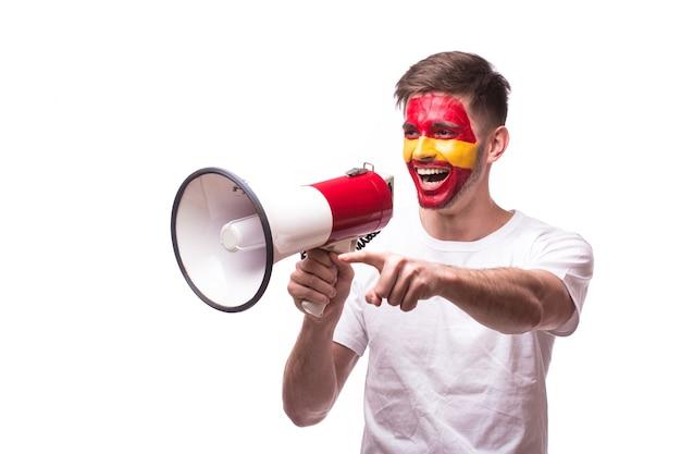 Aficionado al fútbol joven español con megáfono aislado en la pared blanca