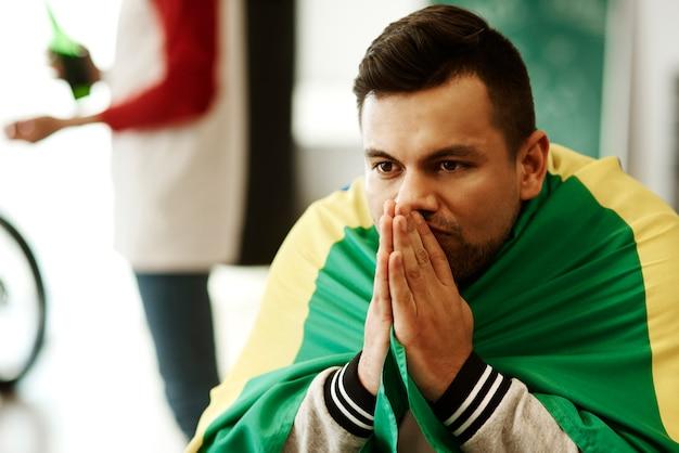 Aficionado al fútbol nervioso con bandera rezando