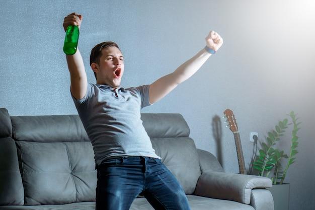 Aficionado al fútbol viendo televisión en un autocar con cerveza y gritando gol