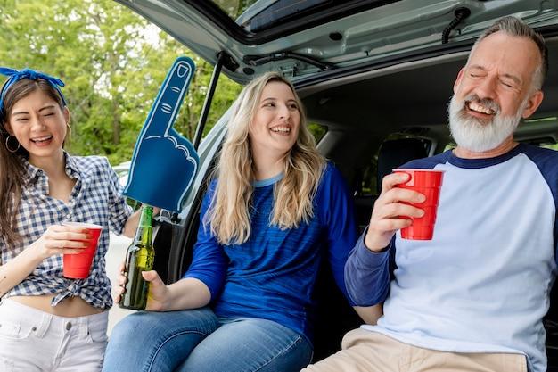 Los aficionados al béisbol sentados y bebiendo en el maletero del coche en una fiesta en el portón trasero