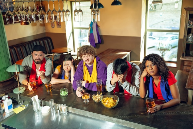 Aficionados al deporte animando en el bar, pub y bebiendo cerveza mientras ven una competición deportiva.