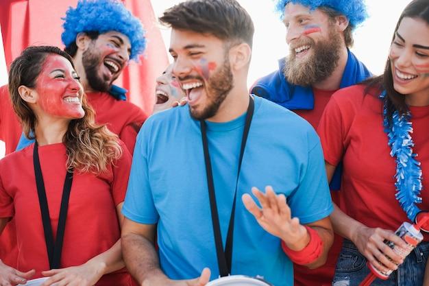 Aficionados al deporte locos gritando mientras apoyan a su equipo fuera del estadio - concéntrese en la cara de la niña izquierda