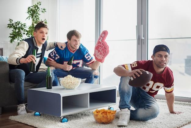 Aficionados al fútbol americano frente a tv