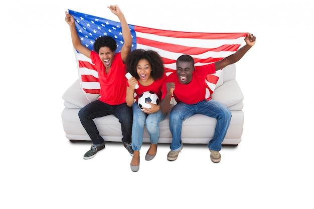 Aficionados al fútbol americano en rojo en el sofá