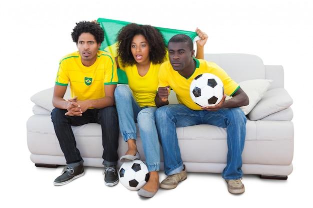 Aficionados al fútbol brasileños en amarillo sentado en el sofá
