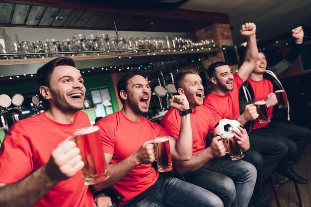 Aficionados al fútbol celebrando y animando bebiendo cerveza