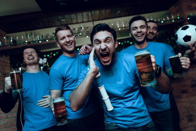 Aficionados al fútbol celebrando gol y bebiendo cerveza.