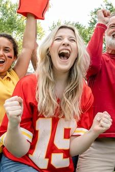 Aficionados al fútbol celebrando la victoria de su equipo en una fiesta en el portón trasero