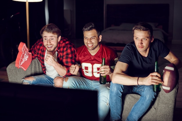 Aficionados al fútbol emocionados viendo fútbol americano por la noche