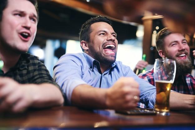 Aficionados al fútbol emocionados viendo fútbol americano en el pub