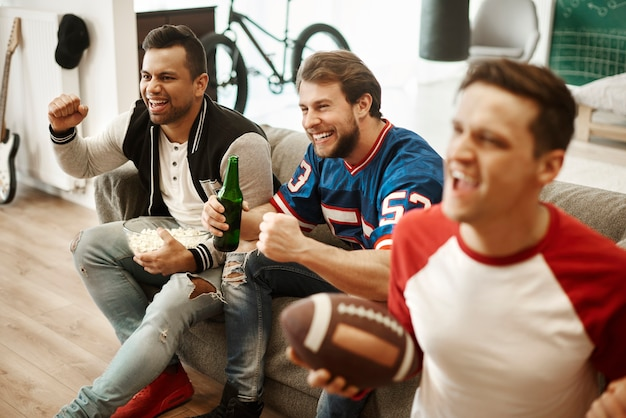 Aficionados al fútbol emocionados viendo fútbol americano