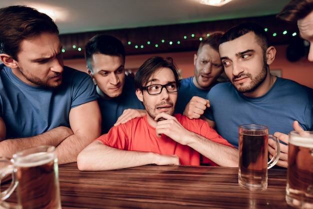 Aficionados al fútbol del equipo azul en el bar que rodea al equipo rojo.
