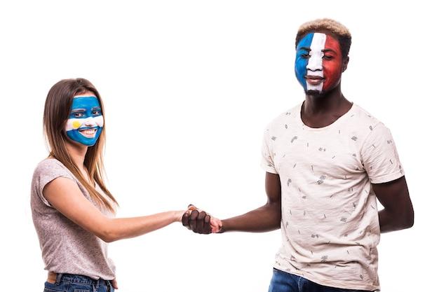 Los aficionados al fútbol de los equipos nacionales de argentina y francia con la cara pintada se dan la mano sobre fondo blanco.