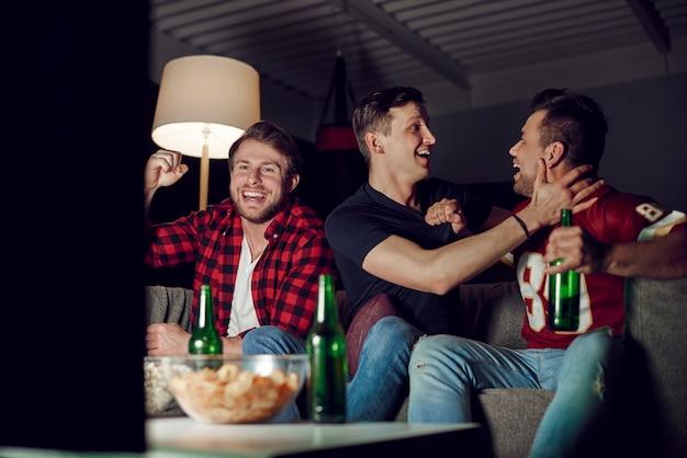 Los aficionados al fútbol extasiados vitoreando en casa