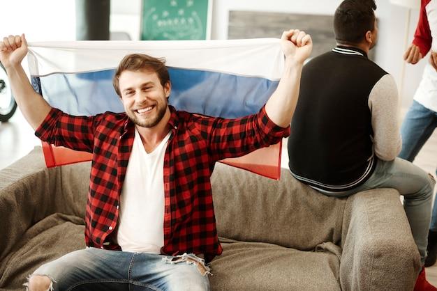 Aficionados al fútbol feliz ondeando una bandera rusa