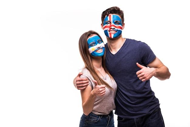 Los aficionados al fútbol partidarios con la cara pintada de los equipos nacionales de argentina e islandia aislado sobre fondo blanco.