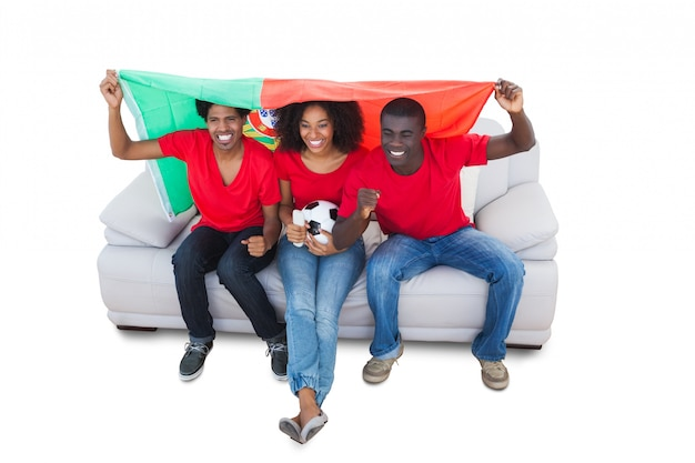 Aficionados al fútbol de portugal en rojo en el sofá