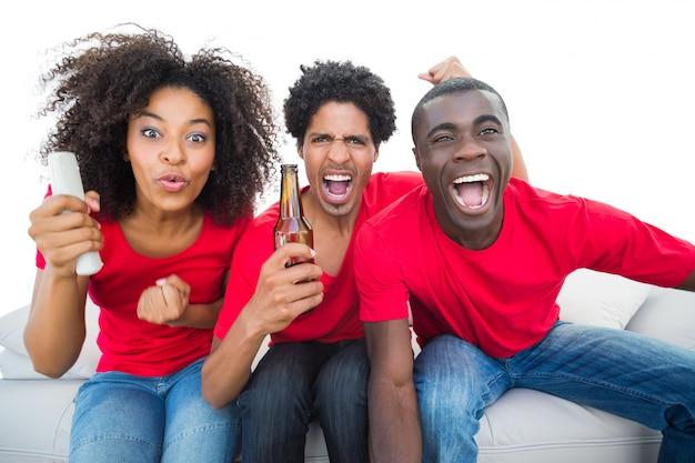 Aficionados al fútbol en rojo animando en el sofá con cervezas