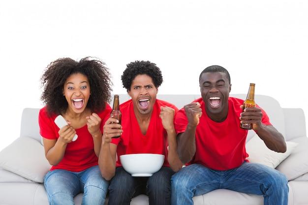 Aficionados al fútbol en rojo animando en el sofá