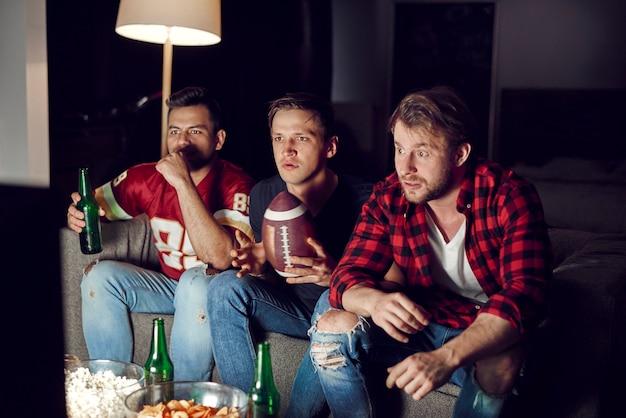 Aficionados al fútbol viendo partido con cervezas y bocadillos.