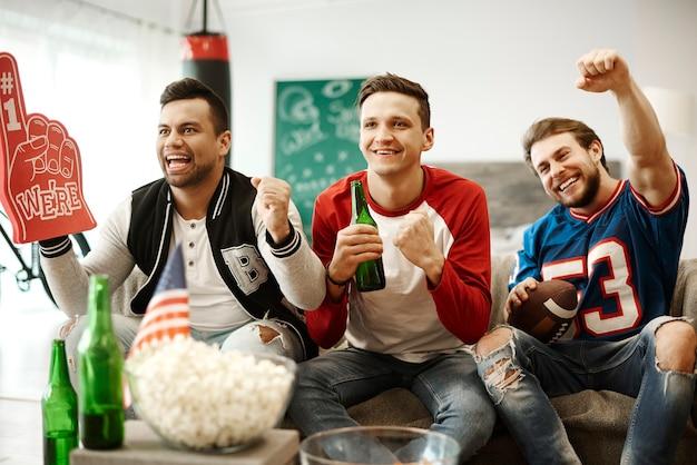 Aficionados al fútbol vitoreando en casa Foto gratis