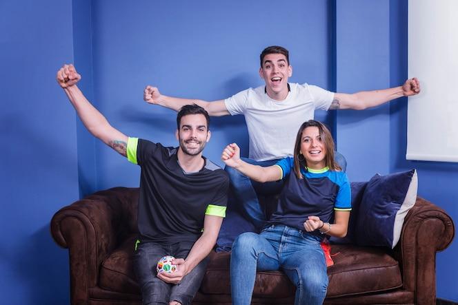 Aficionados celebrando en sofá