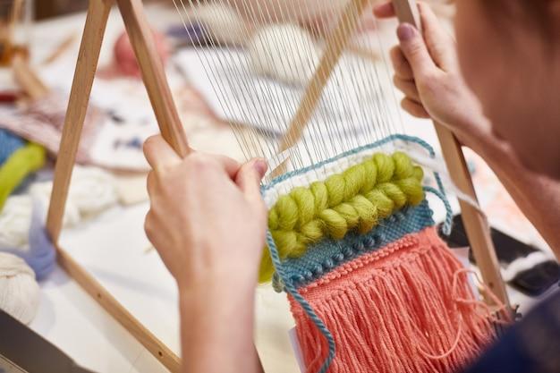 Aficiones. mano de la mujer. lazo de tejer alfombra de lana.
