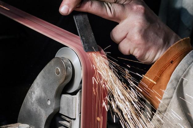 Afilado de cuchillas creando en un proceso de lijadora de banda.