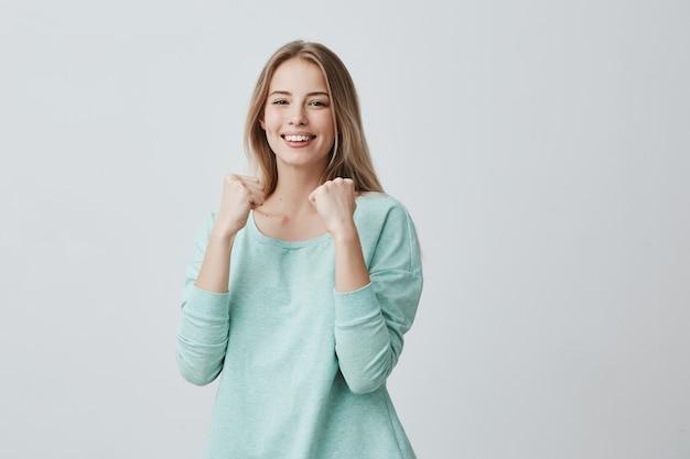 Afortunada joven empleada que disfruta el éxito en el trabajo, sonriendo ampliamente, manteniendo los puños cerrados. hermosa mujer rubia en suéter azul claro sintiéndose feliz y emocionada posando