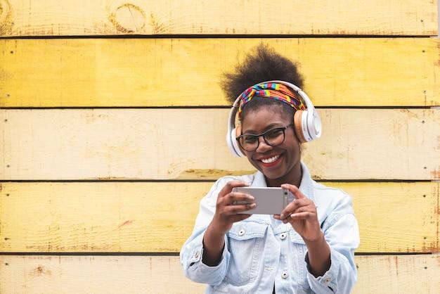 Afro americana adolescente usando teléfono móvil al aire libre