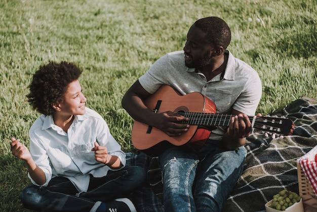 Afro father play on guitar y looking on son en picnic.