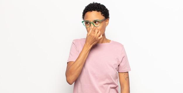 Afro joven mujer negra sintiéndose disgustada, tapándose la nariz para evitar oler un hedor desagradable y desagradable