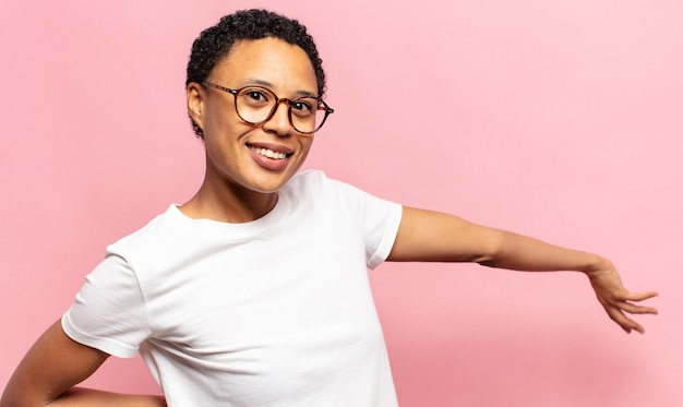 Afro joven mujer negra sintiéndose feliz y alegre, sonriendo y dándote la bienvenida, invitándote con un gesto amistoso