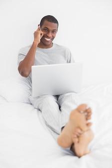 Afro joven usando teléfono celular y computadora portátil en la cama