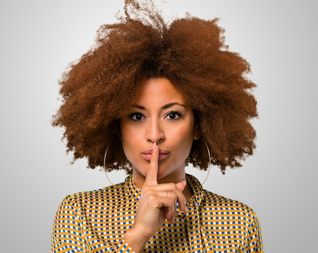 Afro mujer haciendo un signo de silencio