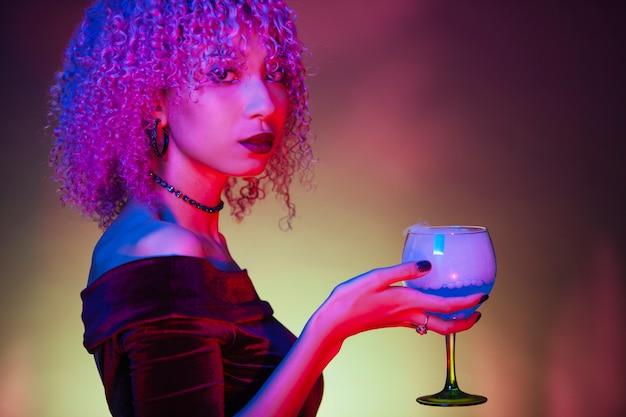 Afro oscura mujer sosteniendo una bebida misteriosa alcohólica
