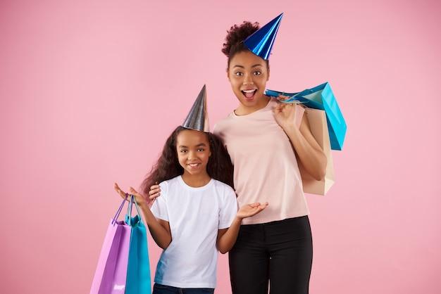Afroamericana madre e hija en gorros de vacaciones