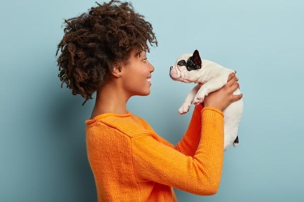 Afroamericana vistiendo suéter naranja con perro