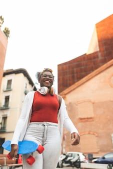 Afroamericano adolescente caminando y llevando el monopatín al aire libre.