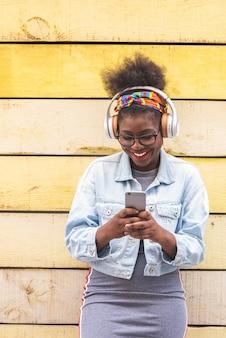Afroamericano adolescente utilizando teléfono móvil al aire libre.