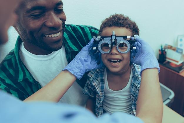 Afroamericano padre con hijo en recepción oftalmólogo