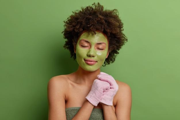 Afroamericano tranquilo con cabello rizado y tupido sostiene guantes de baño envueltos en una toalla suave aplica mascarilla humectante verde