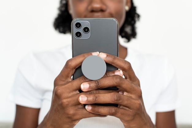 Agarre de teléfono redondo detrás del móvil con mujer afroamericana enviando mensajes de texto en el teléfono