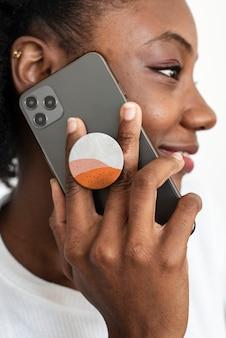 Agarre de teléfono redondo detrás del móvil con mujer afroamericana hablando por teléfono