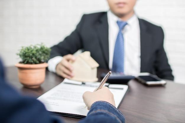 Agencia bancaria que explica a la gente del préstamo hipotecario y al contrato de firma del comprador