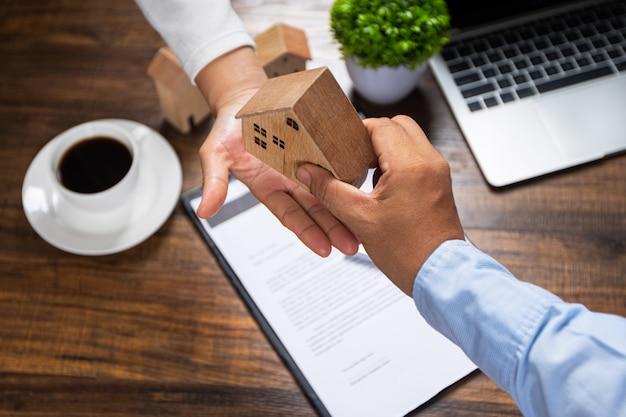 La agencia del banco de negocios mantiene el modelo de la casa y le da una propuesta al cliente, un préstamo de vivienda con un interés económico para la compra de una casa y un contrato de condominio terminado del concepto de bienes raíces.