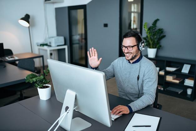 Agente de atención al cliente saludando a sus clientes a través de videollamada.
