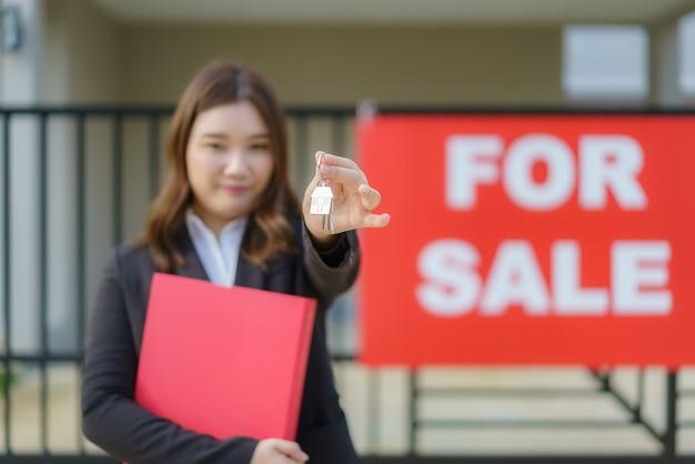 Agente de bienes raíces asiático o mujer inmobiliaria sonriendo y sosteniendo un archivo rojo con la llave de la casa que muestra en frente de la casa.
