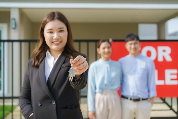 Agente de bienes raíces asiático o mujer inmobiliaria sonriendo y sosteniendo un archivo rojo