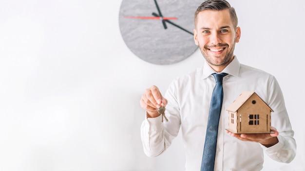 Agente de bienes raíces con casa y llaves